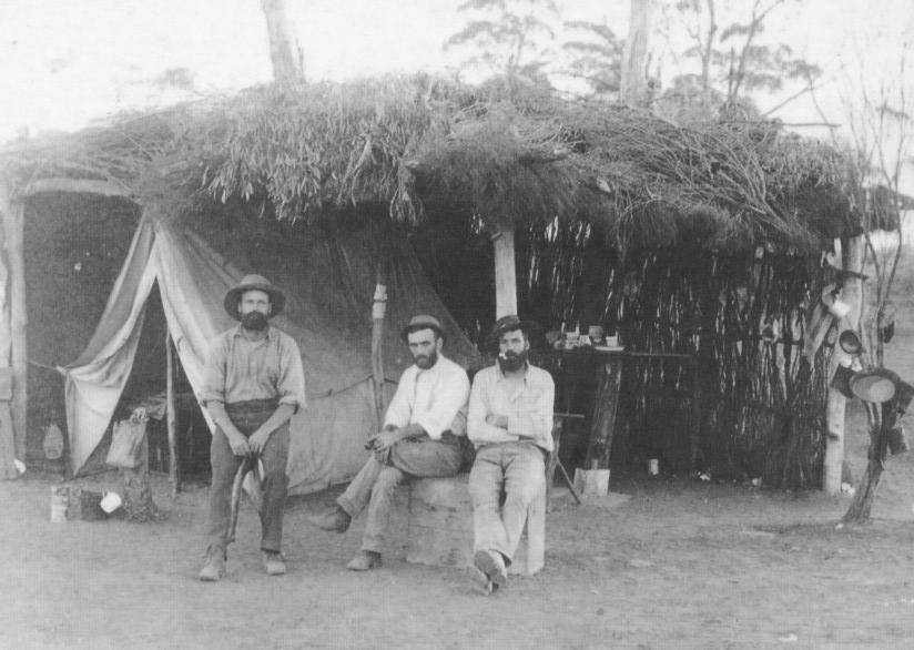 Douglas William GRAY and friends outside their prospecting camp 1898-99, bushcamp tent covered in brush, canvas water bay, billy and enamel cup. Taken by Rembrant Photo Co, donated by daughter of  DW Gray Jessie Gray 1989.