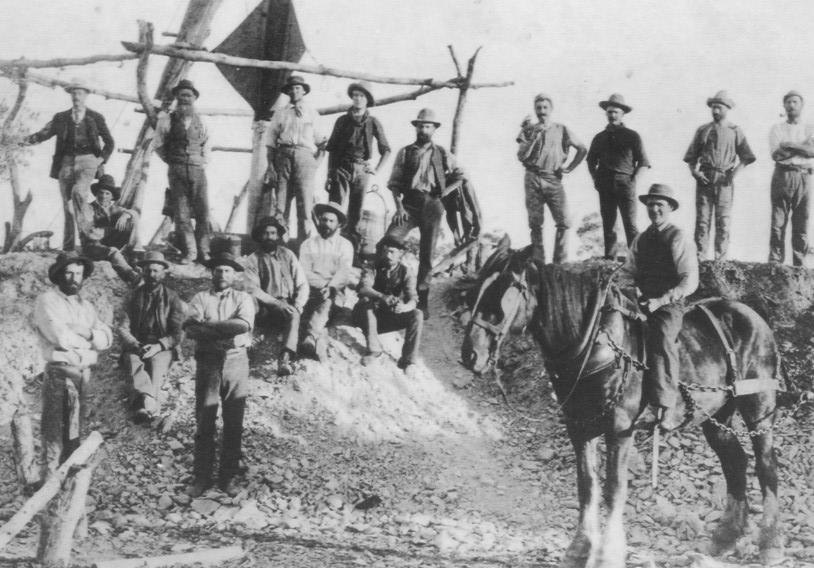 Slug Hill Grand Junction Mine about 1898. Group of 17 miners beside wooden frame and windsail, ore bucket, horse in full harness on right  Donated by Jessie Gray in 1989. Photo by Rembrant Photo Co.