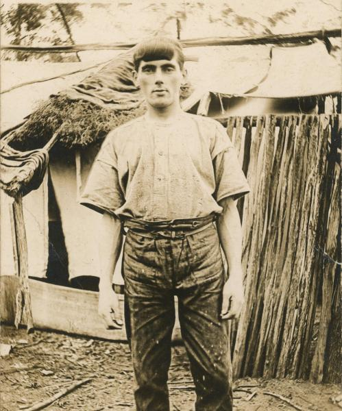 PHOTOGRAPH, B&W, postcard print, Matthew Harwood standing in front of improvised canvas, hessian and bush wood tent/ house, Canning Vale