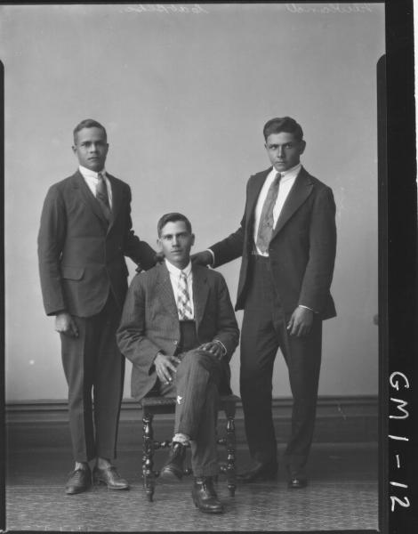 Portrait of three young men in suits, F/L 'Newland', one sitting on chair other standing.