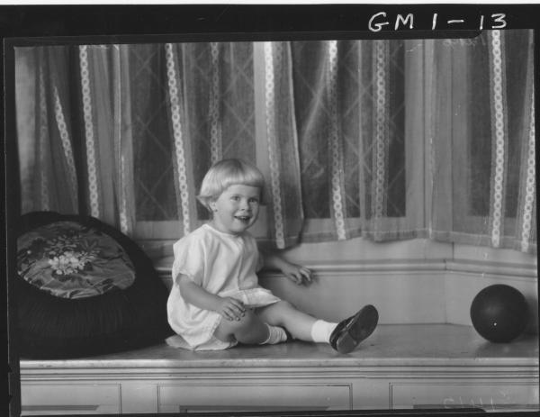 Portrait of child in dredd sitting on window seat, F/L ,'Newman'.
