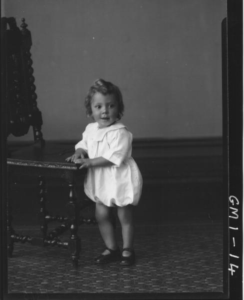 Portrait of a child in dress leaning on chair, F/L,'Wilson'.