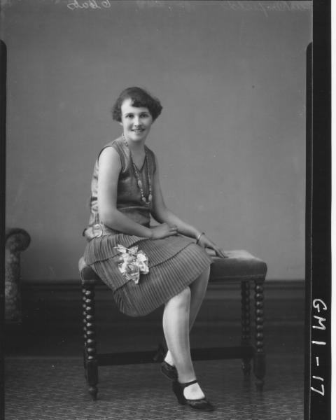 Portrait of a young woman sitting on a seat, F/L,'Whinfield'; sleeveless dress with flower and leaves attached to skirt