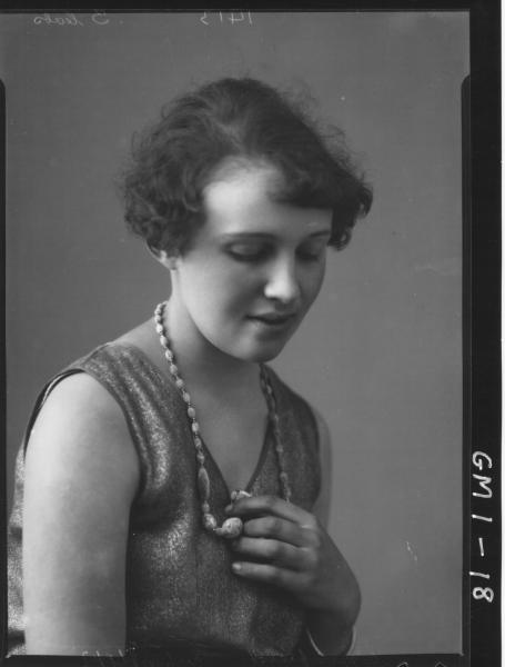Portrait of a young woman in a sleeveless dress, H/S, 'Whinfield'; holding necklace.