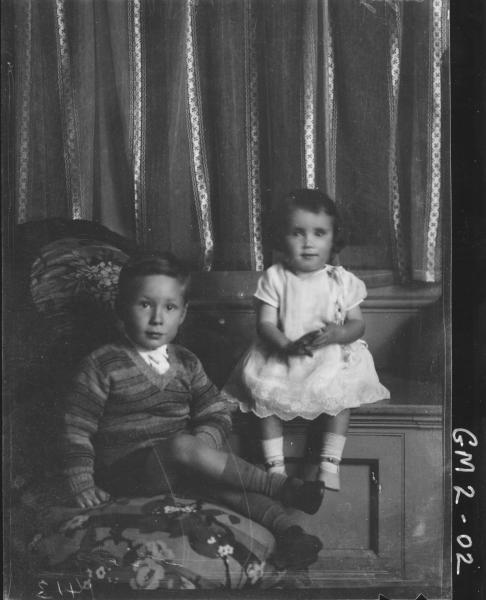 Portrait of two young children,'Quigley'; boy sitting on chair, girl on window seat.