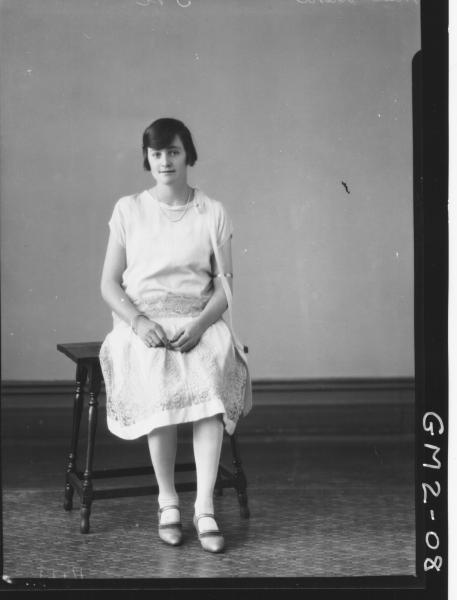 Portrait of young woman in short sleeve dress, F/L, Miss'Ward' seated on small table.
