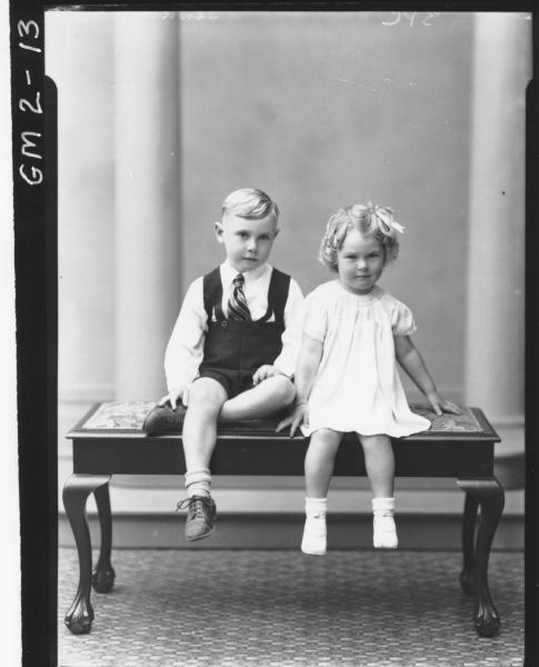 Portrait of dressed up young boy and girl sitting on cushioned bench, F/L,'Jenkins'.