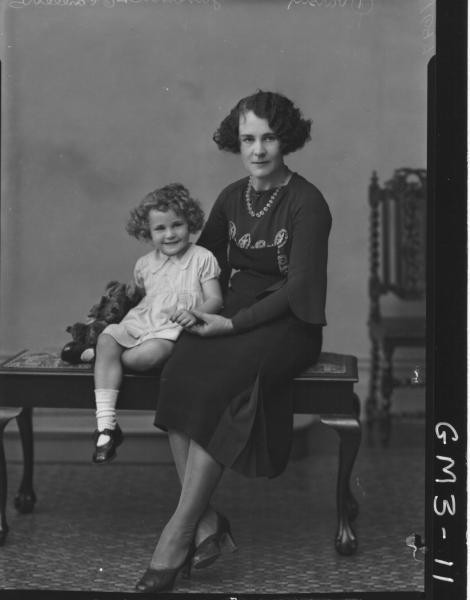 Portrait of woman in long sleeved dress and young girl, F/L, 'Junevitch'. Sitting on cushioned bench.