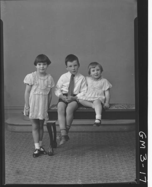 Portrait of two young girls in dresses and young boy in shirt and tie, sitting on cushioned bench, F/L, 'Illingworth'.