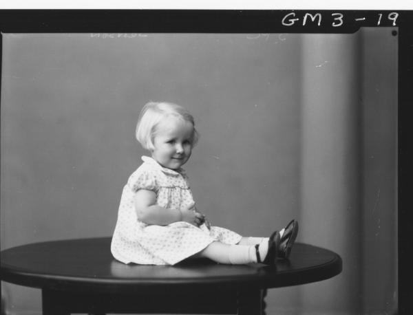 Portrait of young girl, F/L, 'Jenson'. In dress, sitting on table.