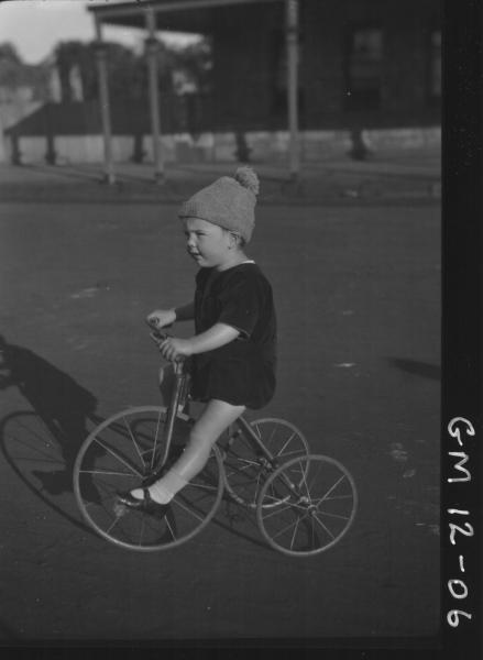 Street view of young child riding a tricycle, F/L 'Dunstan'
