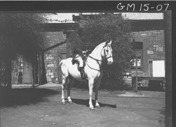 man in riding costume on horse outside stone house, 'Hill'