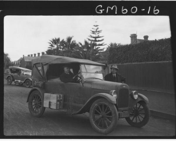 Motor car 62 35 with two men outside houses