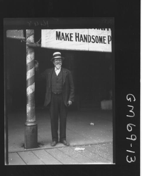 OLD MAN STANDING OUTSIDE SHOP