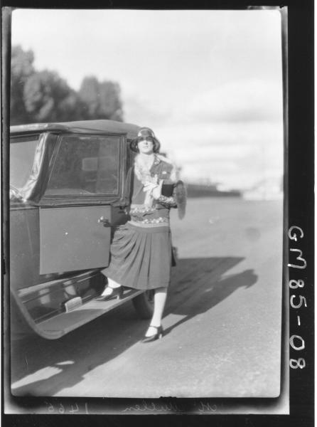 WOMAN STANDING BESIDE CAR, MCMULLEN