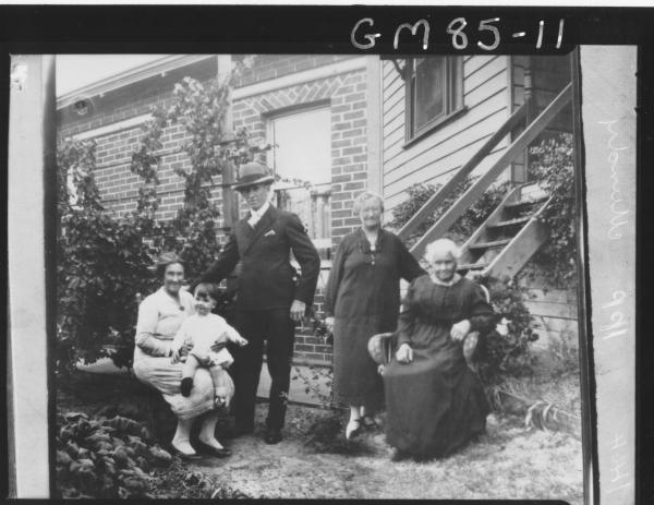 COPY OF THREE WOMEN, MAN AND CHILD OUTSIDE HOUSE, MUNDY