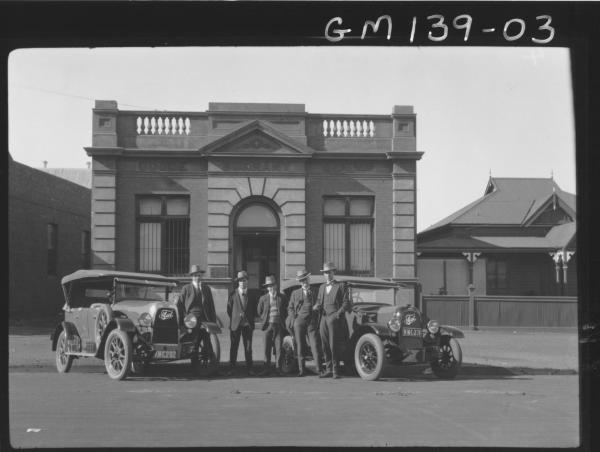 Men and motorcars outside Goode Durrant & Co. Office