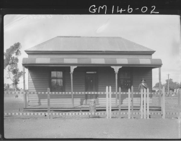 Man standing on verandah of house 'Carson'