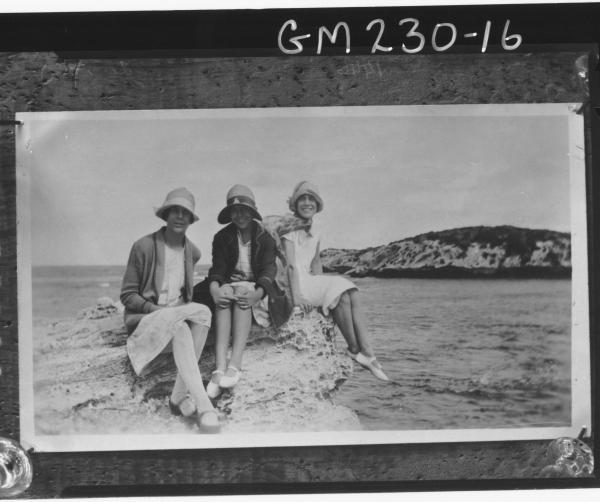 Copy of three women 'Jones' sitting on rocks by the sea