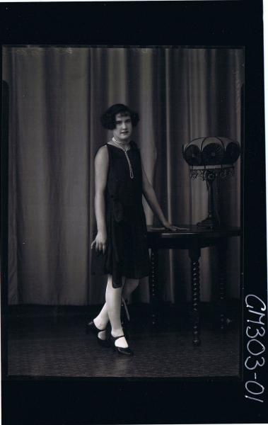 F/L Portrait of woman standing, wearing knee length dress; 'Screen'