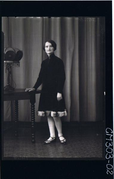 F/L Portrait of woman standing, wearing knee length velvet dress with fur hemline; 'Screen'