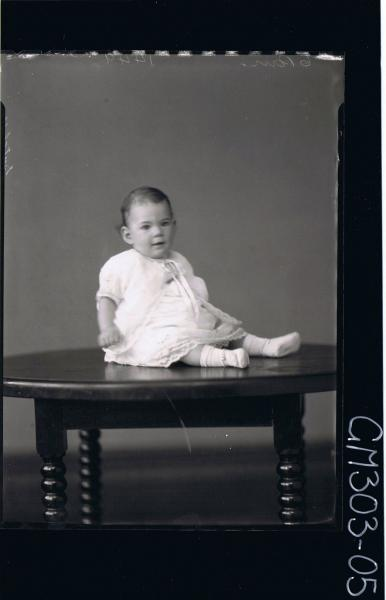 F/L Portrait of baby seated on table, wearing dress, socks, booties; 'Sutcliffe'