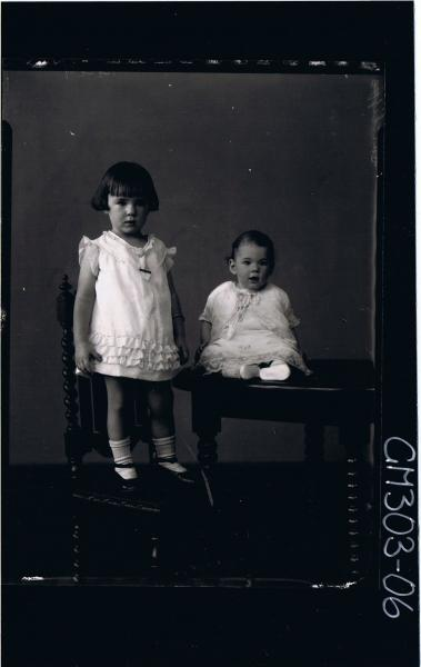 F/L Portrait of female child standing on chair wearing short dress, baby seated on table; 'Sutcliffe'