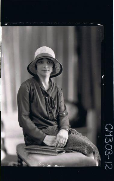 1/2 Portrait of woman, seated, wearing blouse, skirt, hat; 'Sloan'