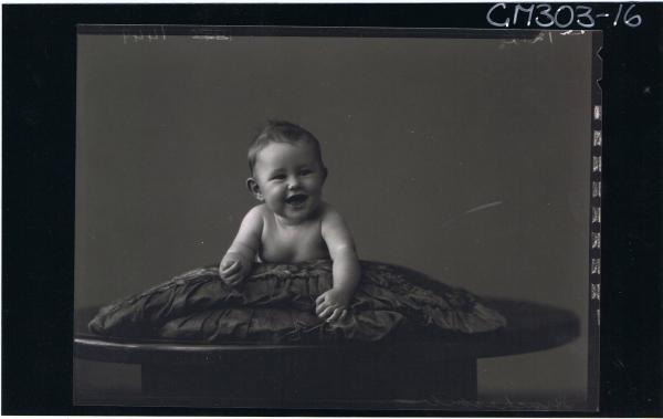 F/L Portrait of naked baby lying on table; 'Stinchcombe'
