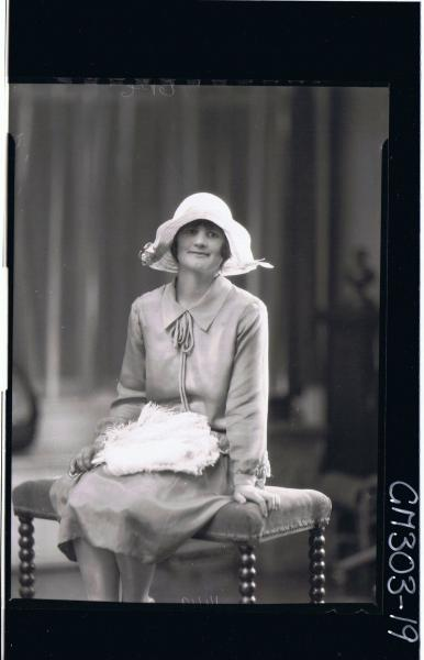 3/4 Portrait of woman, seated wearing three quarter length dress, holding feather fan; 'Smith'