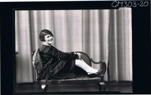 F/L Portrait of woman wearing satin dress, seated on lounge, 'St John'