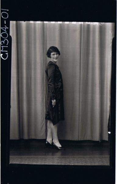 F/L Portrait of woman standing, wearing knee length satin dress, (side view) 'St.John'