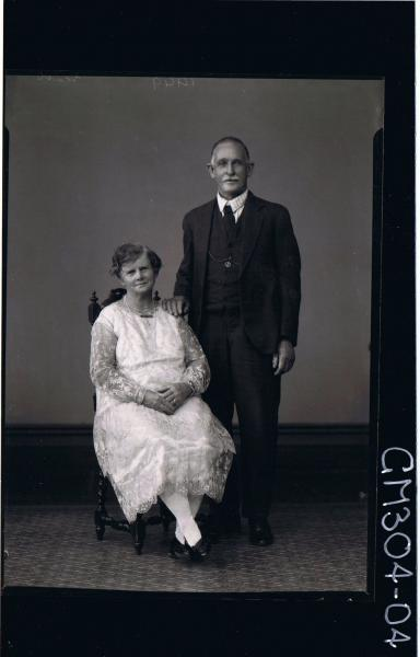 F/L Portrait of man standing wearing three piece suit, woman seated wearing three quarter length lace dress; 'Scott'