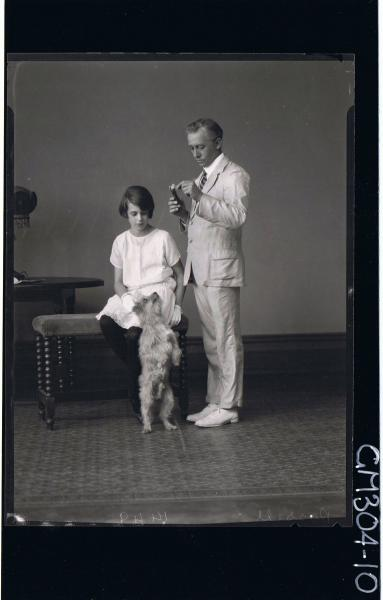 F/L Portrait of girl seated, man standing wearing suit and holding chocolate bar,dog standing on hind legs; 'Rossell'