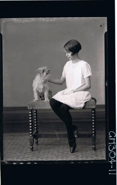 F/L Portrait of girl seated wearing knee length lace dress and gloves, with dog seated; 'Rossell'