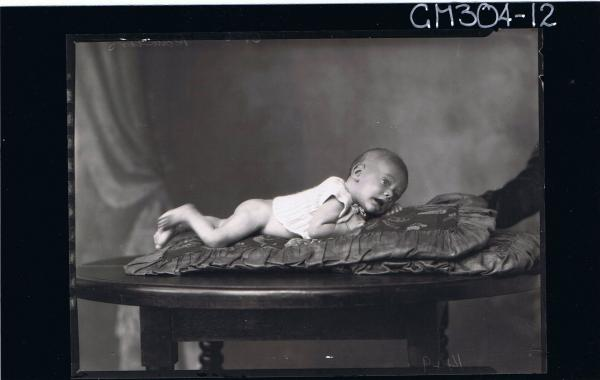 F/L Portrait of baby lying on table wearing knitted top; 'Rawlins'