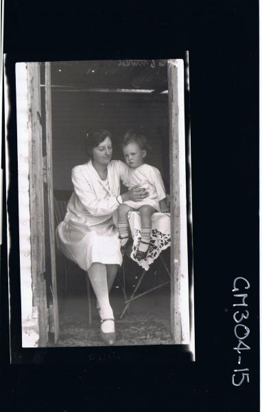 F/L Portrait of woman wearing knee length dress with child seated in doorway of house; Mrs 'Rainey'