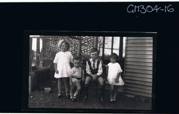 F/L Group Portrait of boy seated, two girls and boy child standing in garden in front of house; 'Robertson'