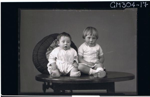 F/L Portrait of baby seated on table, and a child seated also,wearing short lace dress; 'Smythe'
