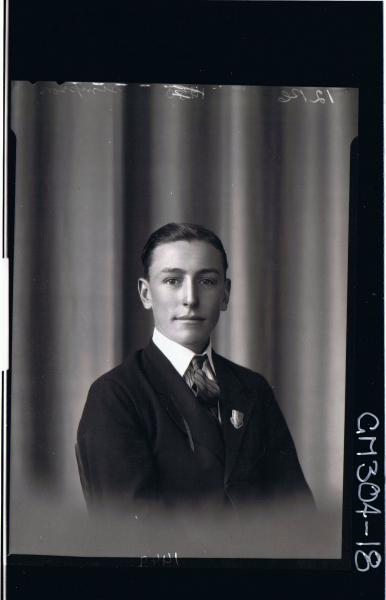 H/S Portrait of young man wearing shirt, tie, jacket with badge on collar; 'Simpson'