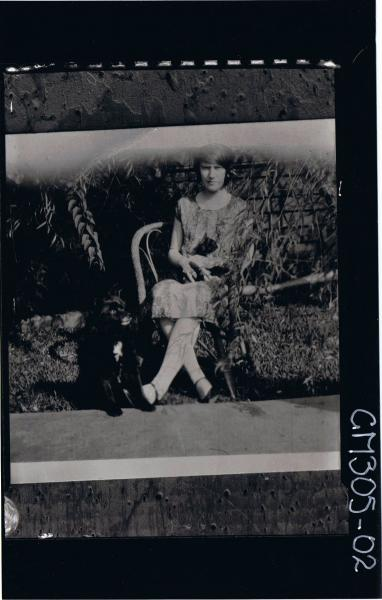 F/L Portrait of woman seated in garden wearing knee length dress with cat on lap and dog seated beside chair; 'Reid'