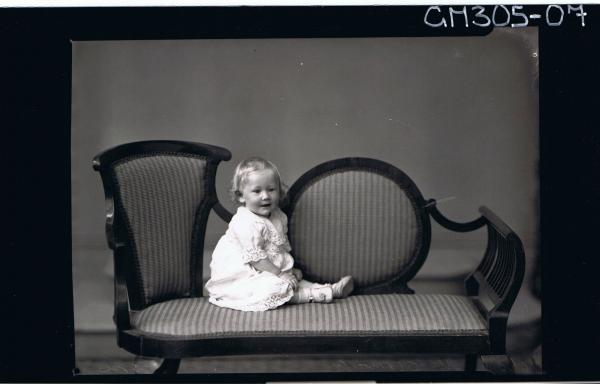 F/L Portrait of baby seated on lounge wearing lace dress; 'McCormack'