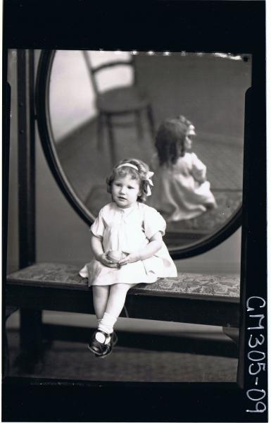 F/L Portrait of girl child seated in front of mirror wearing short dress, ribbon in hair holding a ball; 'McCormack'
