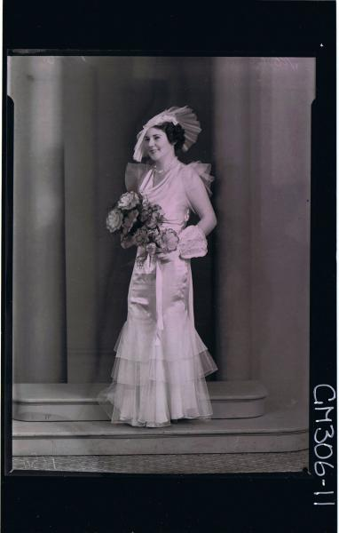 F/L Portrait of bride standing wearing long wedding dress,with 3 tiers,gloves with lace cuffs,holding bouquet 'Mohr' see 306-07