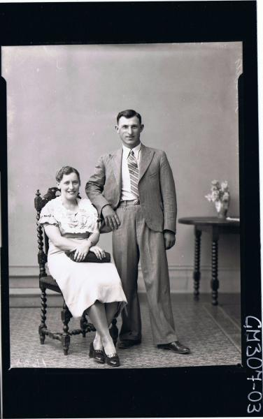 F/L Portrait of man standing wearing suit, woman seated wearing knee length dress, holding handbag; 'Masotti'