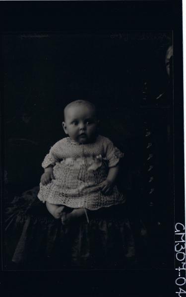 F/L Portrait of baby, seated wearing ankle length dress; 'Schliker'