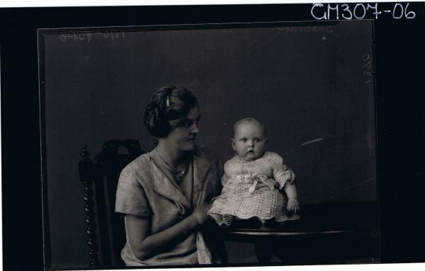 1/2 Portrait of woman seated, with baby seated on table; 'Schliker'