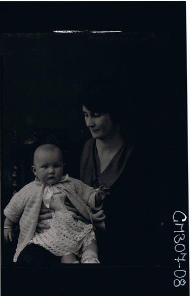 3/4 Portrait of woman seated, holding a baby, wearing dress & cardigan; 'Mrs Sheppard'