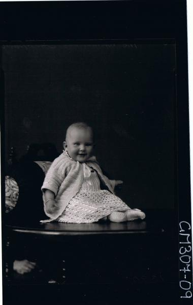 F/L Portrait of baby, seated on table wearing long dress and cardigan; 'Sheppard'