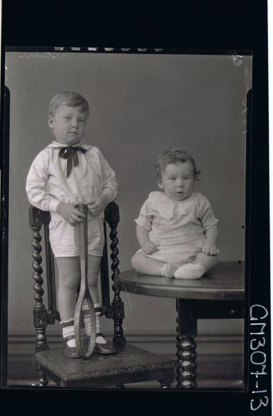 F/L Portrait of baby seated on table, small boy standing on chair wearing shirt, shorts, holding tennis racquet 'Stuber'